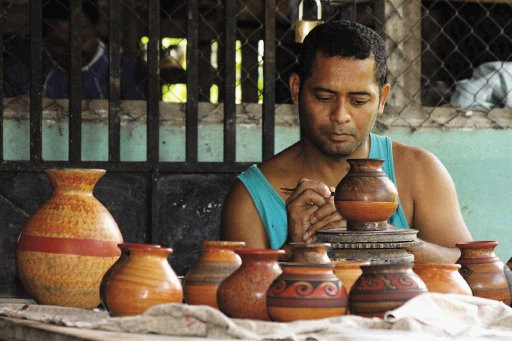man painting some guaitil handmade vessels